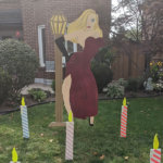 TALL BLONDE LADY WITH LIGHT POST LAWN SIGN